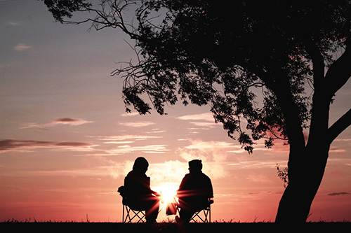 Two people sitting in chairs looking at a pink sunset