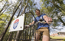 UWG Student riding through campus on a UWG branded bike.