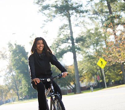 Photo of University of West Georgia student supporting sustainability by riding a bike through campus