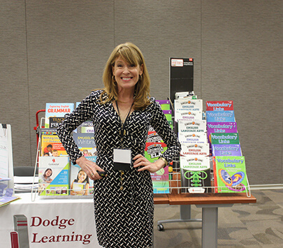 Photo of children's author Kate Klise standing in front of books at the University of West Georgia's Literacy and Beyond conference.