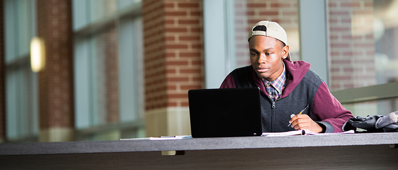 Male student working at a laptop