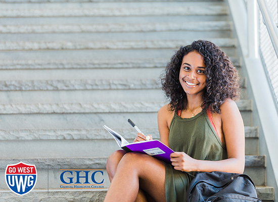 Photo of a student writing in a notebook with the UWG and GHC logos in the left bottom corner