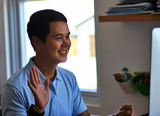 Person smiling and waving in front of computer screen