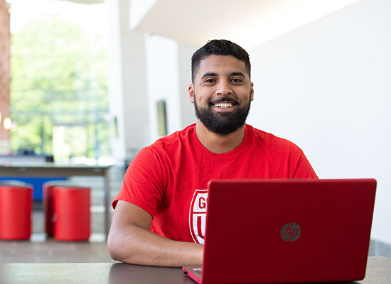 Smiling student working at a laptop
