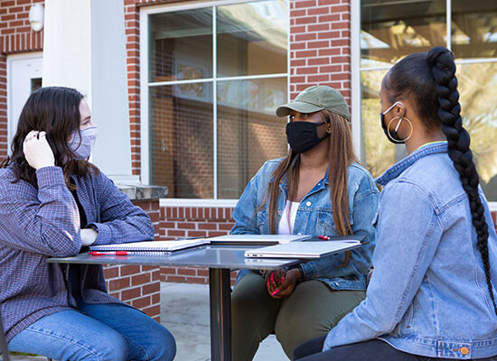 Masked students sitting outside at a table