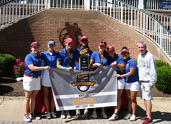 Women golfers holding up a championship banner