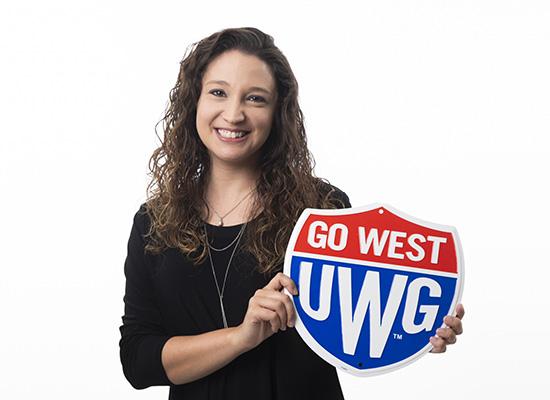 Amanda Wright holding a Go West UWG shield sign