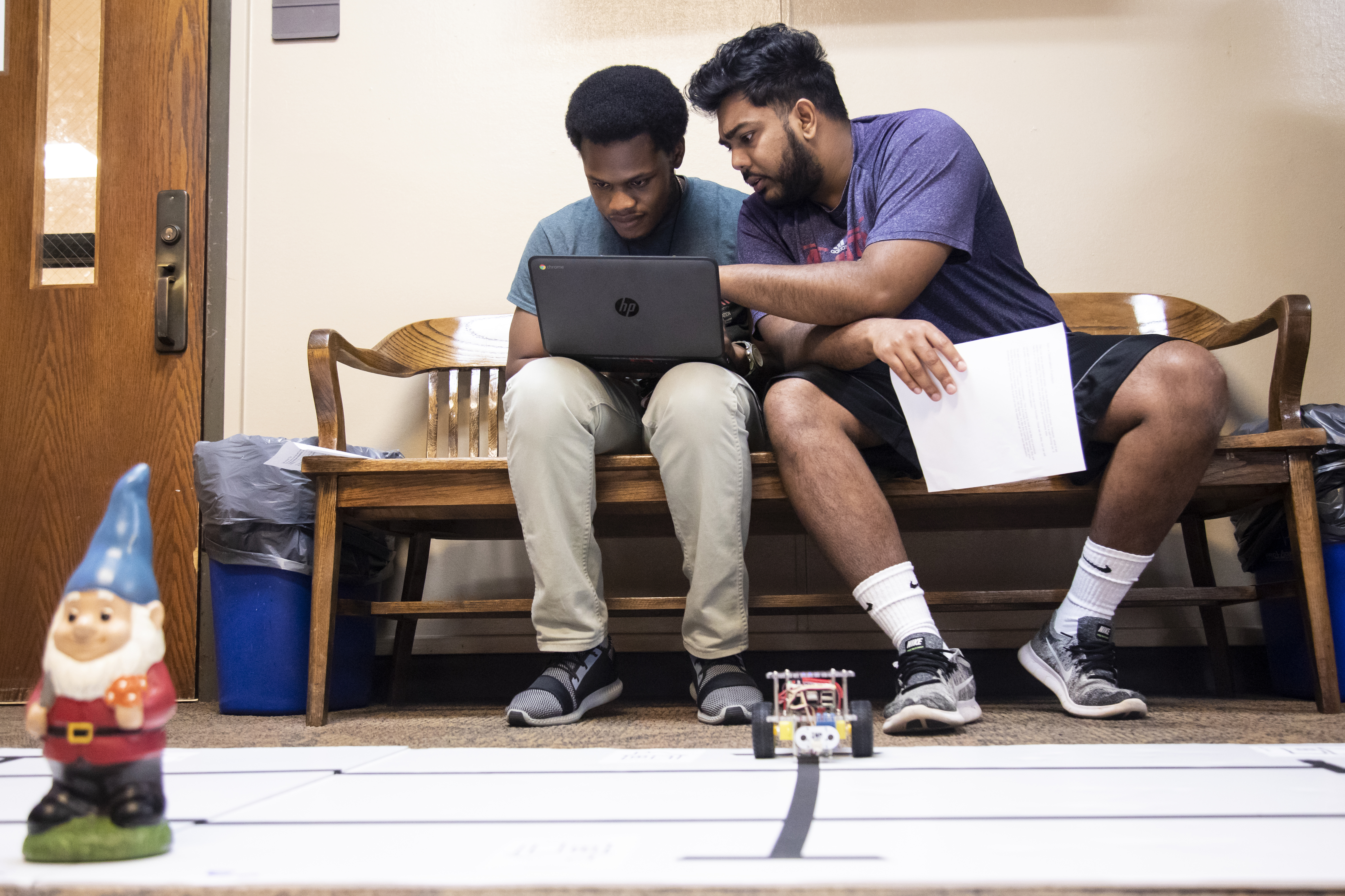 Two male UWG students work on a laptop