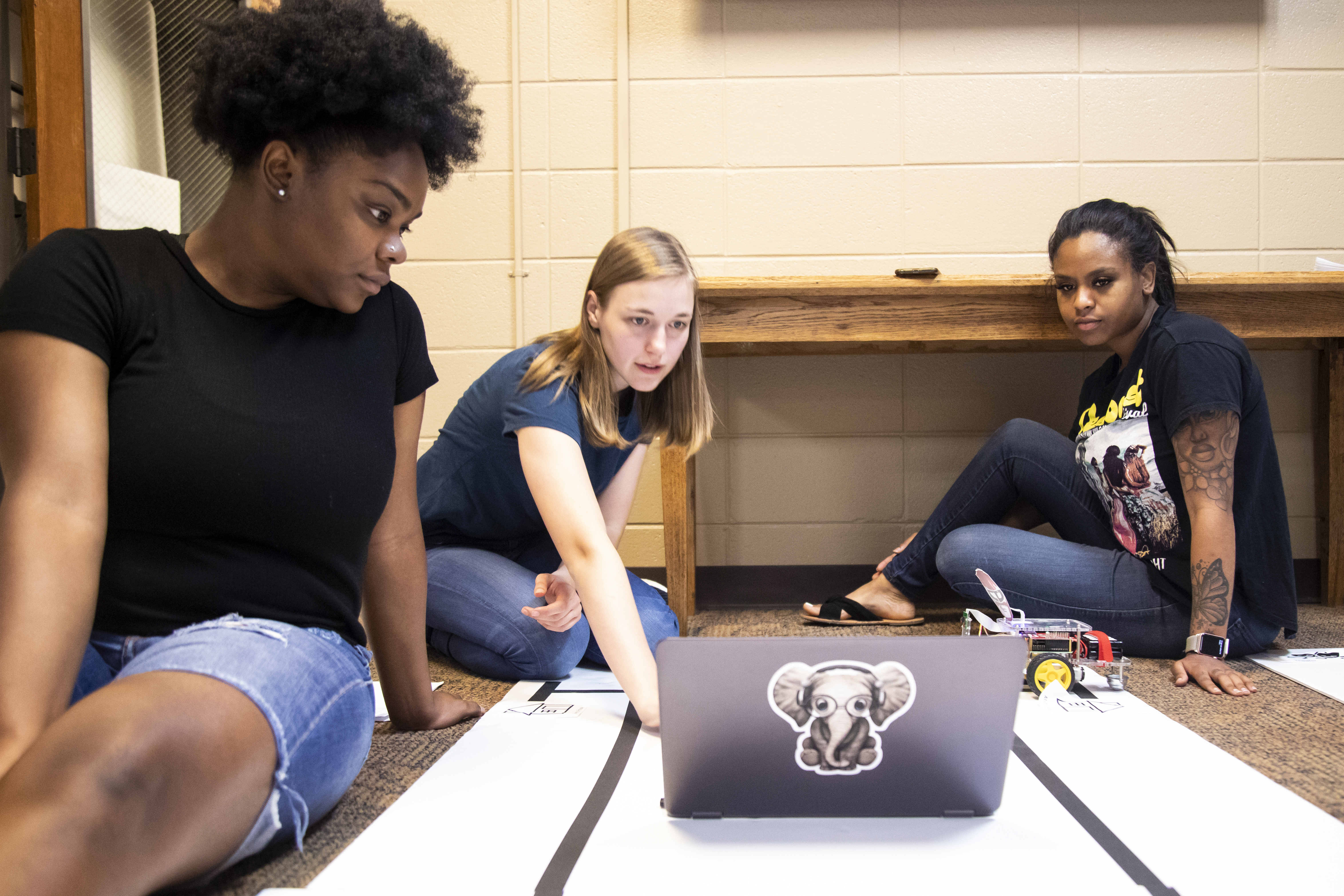 Three female UWG students work on a laptop
