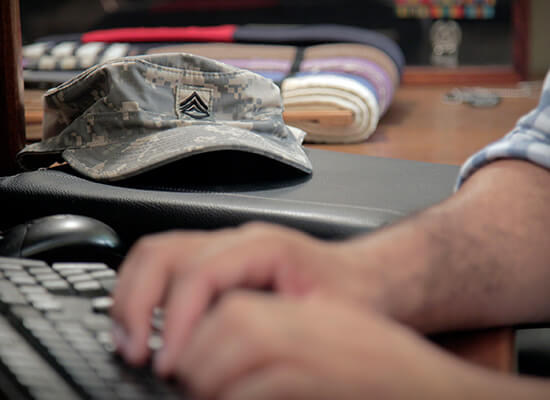 A veteran typing at a computer with a military hat in the background