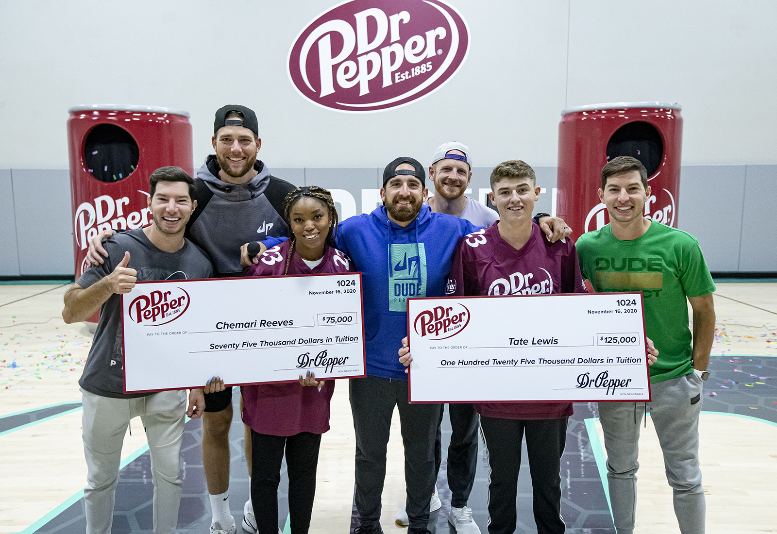 Winners of Dr Pepper contest hold up checks.