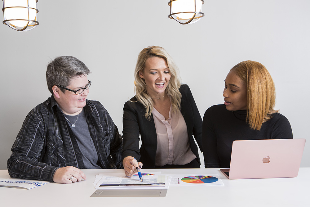 Three UWG Business students collaborate on an assignment together.