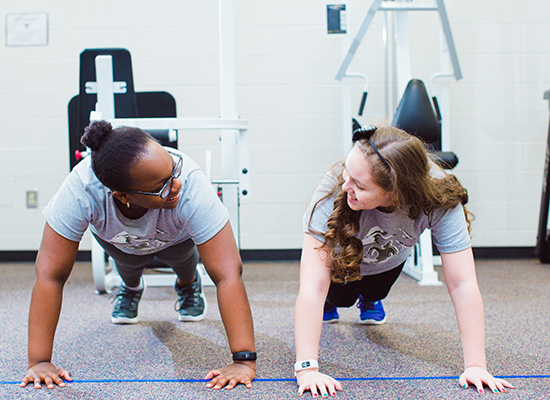 Two UWG students working out at the gym.
