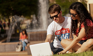 Two students using a laptop outside on grass, in front of campus fountain.