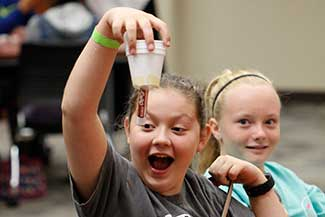 A young student holds up her experiment