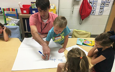 A student teacher helps a child