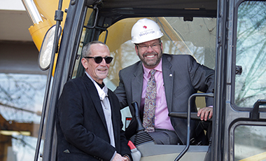 UWG President Dr. Kyle Marrero in a hard hat sits inside a backhoe or frontloader while Biology Department Chair Dr. Christopher Tabit laughs before him.