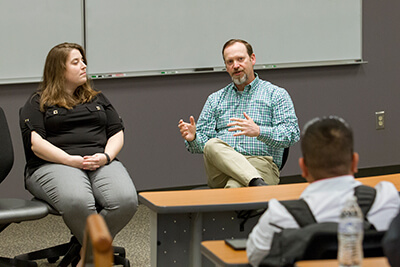 Allyson Cooper and Dr. Jeff Reid, seated, speak before an audience in a classroom.