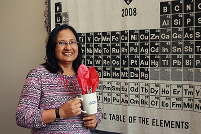 Dr. Basu-Dutt stands with a gift cup, smiling indoors before a periodic trable wall poster.