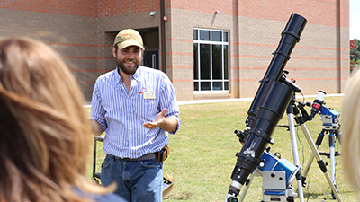 A man in a cap and beard wanders outdoors near some small telescopes