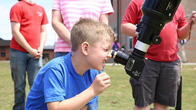 A child squints through the eyepice of a refractor telescope