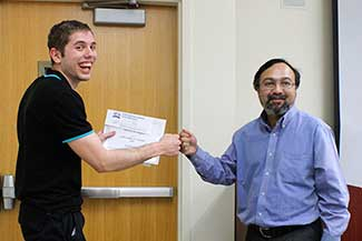Nick Blair smiles enthusiastically as he receives his scholarship from Dr. Farooq Khan, right