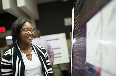 Briana Lewis-Marshall looking at a poster presentation