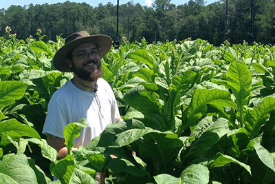 A biology students smiles in a farm field of leafy plants that are as tall as he is.