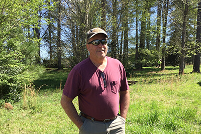 Dr. Gregory Payne stands in a clearing near the woods, casually dressed in sunglasses and a cap.