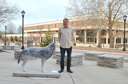 Dr. Hannes Gerhardt stands outside on a clear winter day next to a Howl for UWG wolf statue.