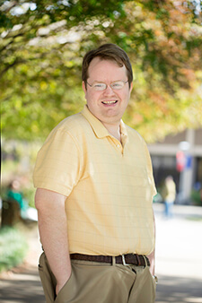 Dr. Logan Leslie poses outdoors on a sunny day while in a yellow shirt.