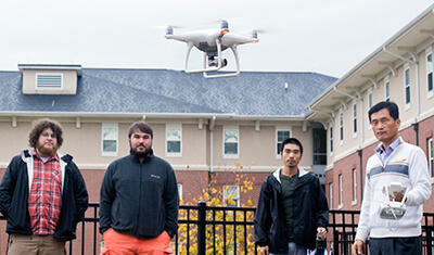 Three student attendees watch as an UAV controlled by Dr. Seong rises over their heads.