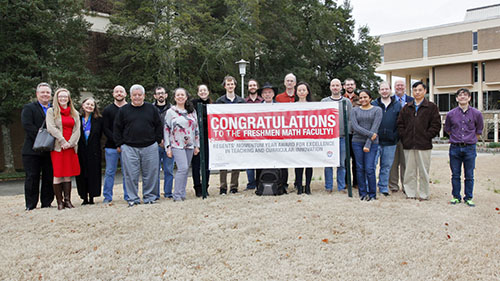 "UWG math faculty and administration hold up a sign that reads ""Congratulations to the Freshmen Math Faculty"""
