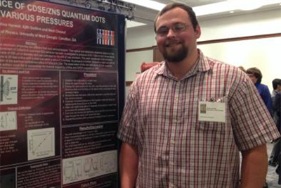 Joshua Harwell stands alongside his poster presentation