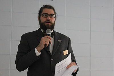 Ben Jenkins in a jacket, tie, beard, and glasses, speaks with a microphone