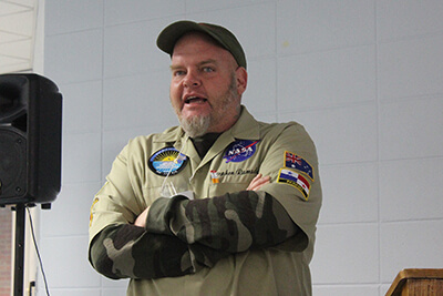 Stephen Ramsden, arms corssed, speaks while wearing a baseball cap and NASA patch
