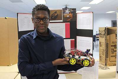 Cordell Palmer stands before his poster project, Reco the Robot, while holding a robotic automobile