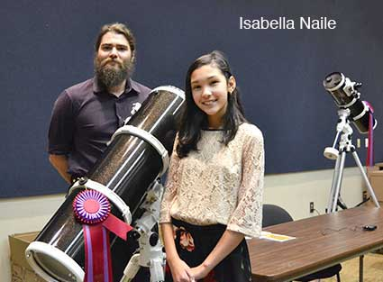 Isabella Naile standing with Ben Jenkins beside her prize, a Cassegrain telescope.