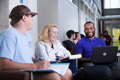 Three students gather around in a public space on UWG's campus to talk and study together
