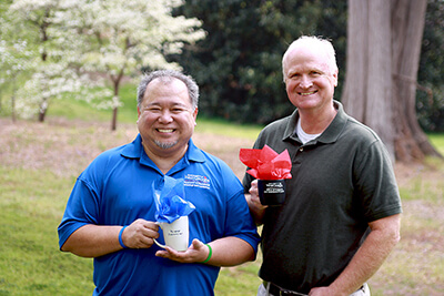 Dr. Danilo Baylen and Dr. Joe Hendricks pose together outdoors holding their UWG gift cups