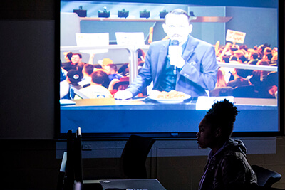 A female student sits in front of a projector screen showing a gaming commentator