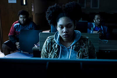 A female UWG student plays a computer game while two male students look on
