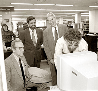 Photo of four men, including former University of West Georgia President Beheruz N. Sethna, standing around a large computer in the Ingram Library, circa mid-1990s