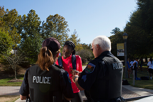 A UWG student smiles with police officers.