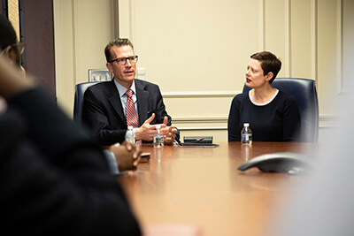 Drs. Brendan and Tressa Kelly speak with student leaders at a conference table.