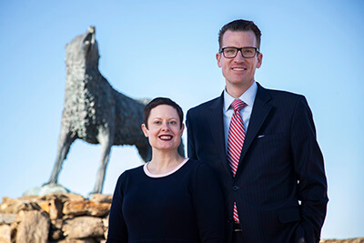 Brendan and Tressa Kelly stand in front of Wolf statue