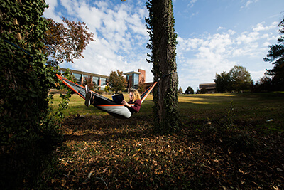 UWG student relaxes in a hammock on campus