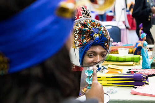 Woman looks at herself in African headwrap in mirror