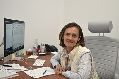 Dr. Stanescu at her office desk with a keyboard, monitior, and sundry papers and other objects.