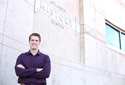 Photo of University of West Georgia alumnus Jess Garbowski standing in front of the Atlanta History Center